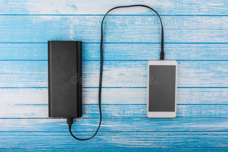 Teléfono elegante blanco moderno con la batería drenada conectada con E grande imágenes de archivo libres de regalías