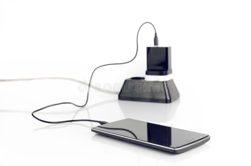 Teléfono elegante con el cargador tapado foto de archivo