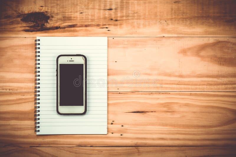 teléfono elegante con el cuaderno en fondo de madera imagen de archivo