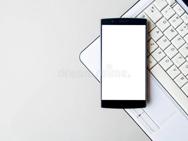 Teléfono elegante con el móvil y el ordenador portátil en blanco El teléfono elegante con la pantalla en blanco y puede ser añade fotos de archivo libres de regalías