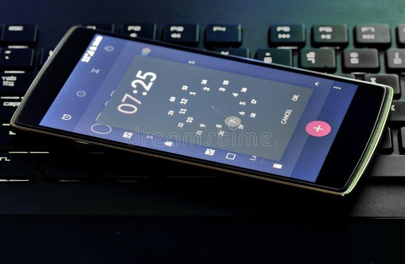 Teléfono elegante con la pantalla del despertador foto de archivo libre de regalías