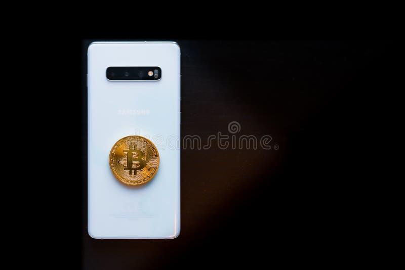 Teléfono elegante con un Bitcoin físico en el top foto de archivo libre de regalías