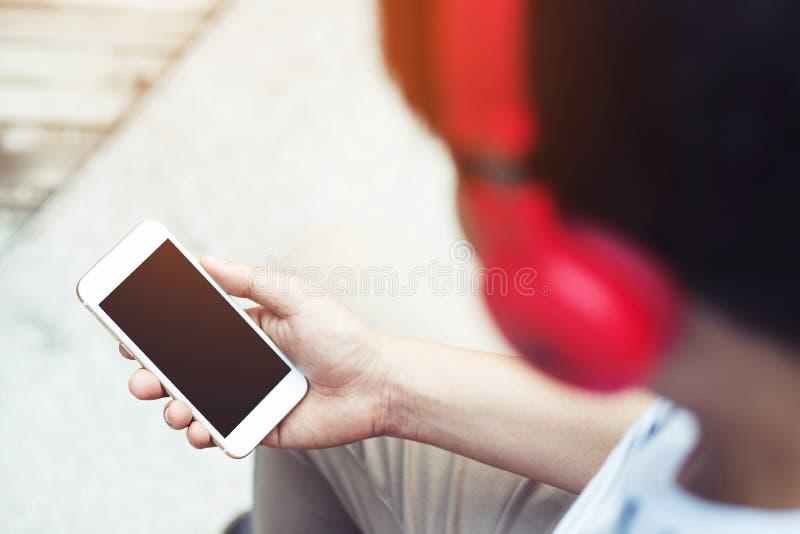 Tel?fono elegante de la mano de la tenencia del hombre joven usando el auricular a escuchar la m?sica imagenes de archivo