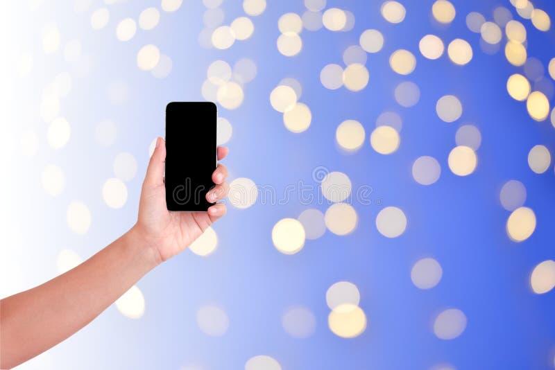 Teléfono elegante de la tenencia de la mano aislado en fondo del bokeh de la noche y luces de la Navidad ligeros abstractos imágenes de archivo libres de regalías