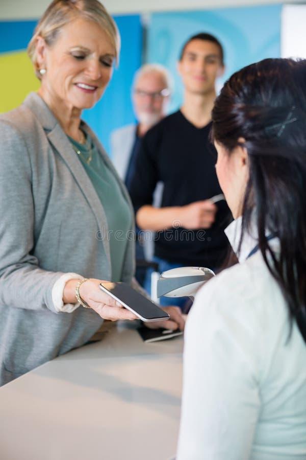 Teléfono elegante de Scanning Barcode On del recepcionista del aeropuerto sostenido por el Pas fotografía de archivo libre de regalías