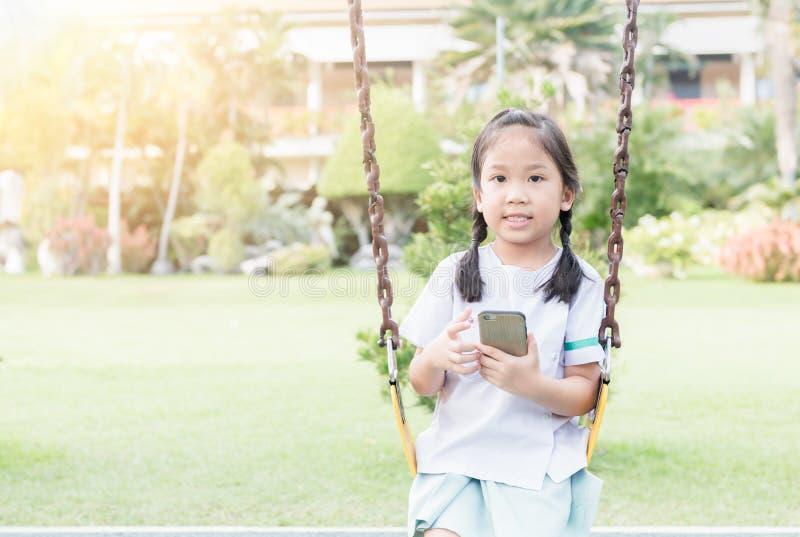 Teléfono elegante del juego lindo de la estudiante en el oscilación foto de archivo