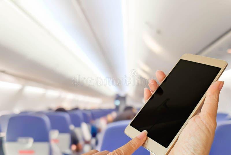 Teléfono elegante del uso de la mano dentro del aeroplano foto de archivo libre de regalías