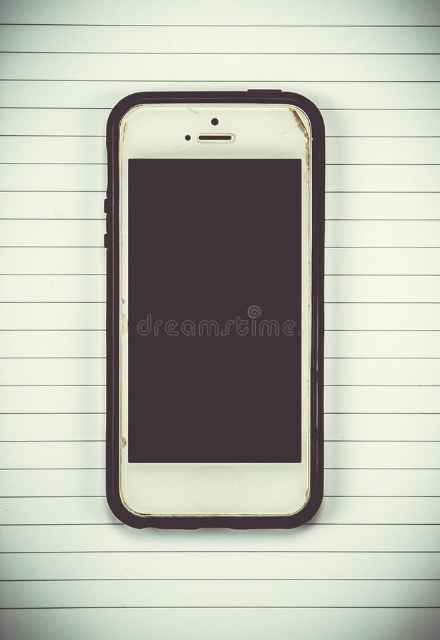 teléfono elegante en fondo del cuaderno foto de archivo