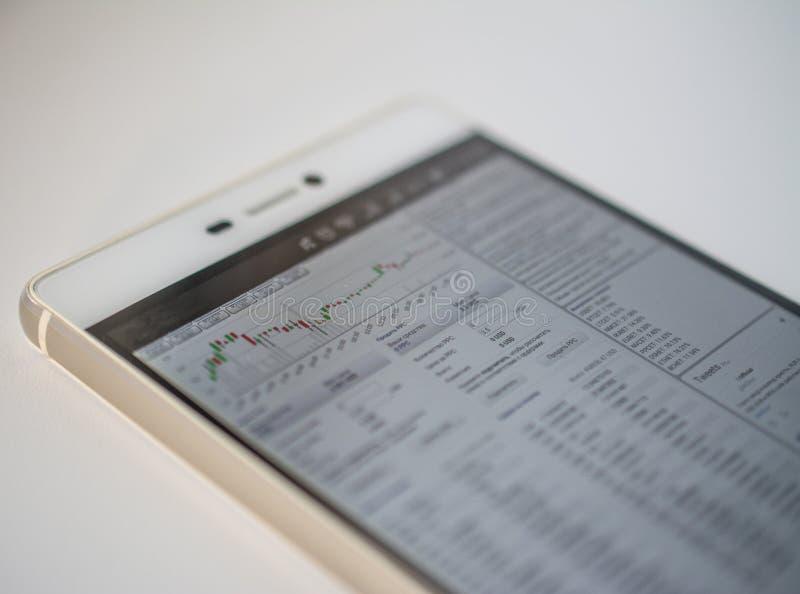 Teléfono elegante en los gráficos de la tabla de los mercados financieros para el crecimiento del bitcoin y de otras crypto-moned fotos de archivo libres de regalías
