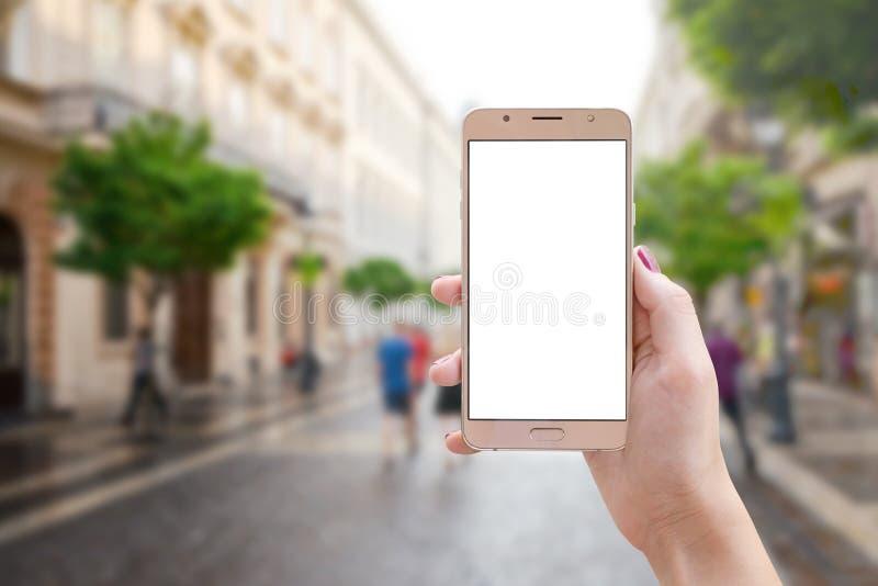 Teléfono elegante en mano de la mujer en la calle de la ciudad fotografía de archivo libre de regalías