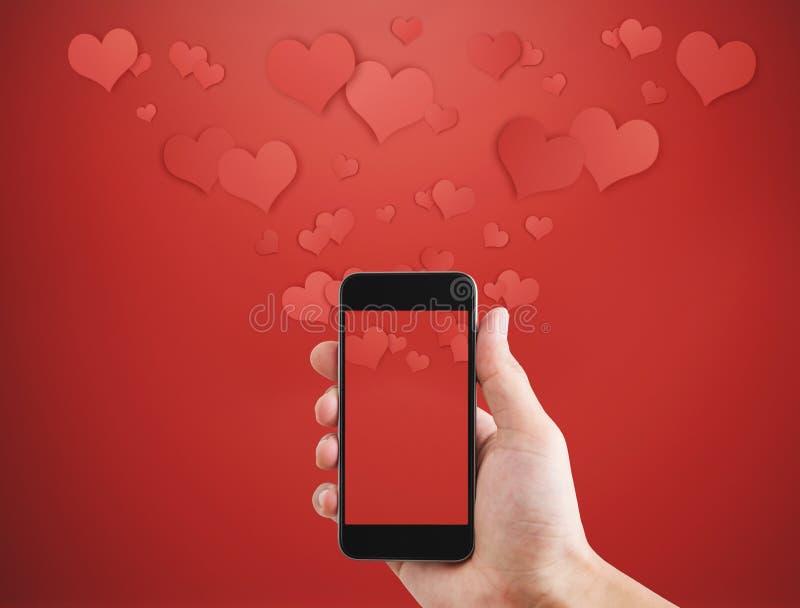 Teléfono elegante móvil, con los corazones flotantes Tarjetas del día de San Valentín, mensaje del amor y concepto que manda un S fotografía de archivo libre de regalías
