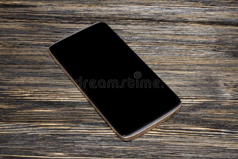 Teléfono elegante negro con la pantalla aislada en el escritorio de madera viejo imagen de archivo