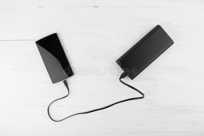 Teléfono elegante negro conectado con el banco grande del poder de batería que carga C fotografía de archivo libre de regalías