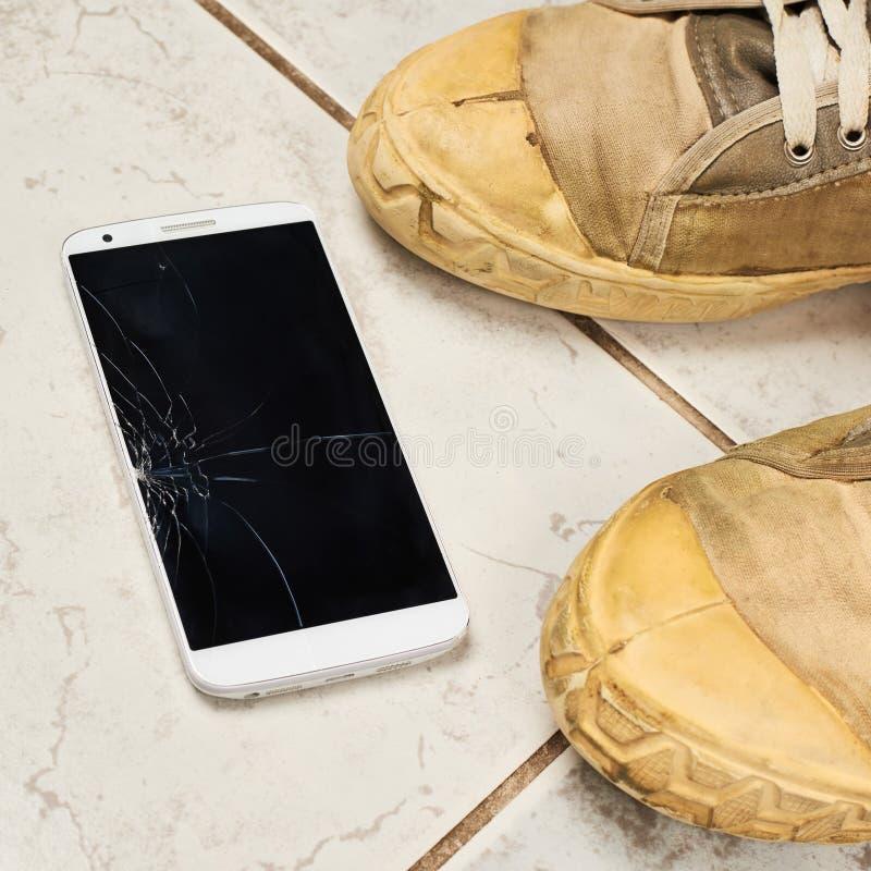 Teléfono elegante quebrado sobre las tejas imágenes de archivo libres de regalías