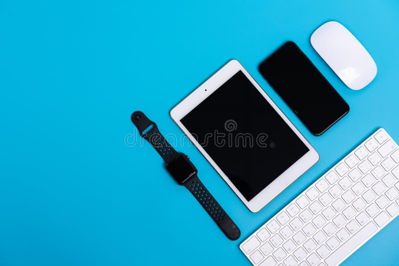 Teléfono elegante, reloj elegante, tableta, ratón y teclado en fondo del azul de cielo fotografía de archivo