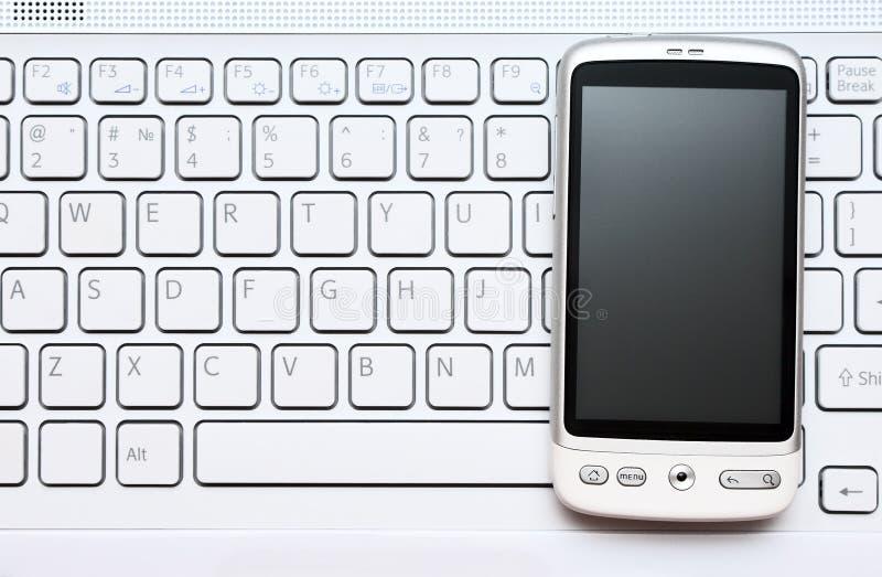 Teléfono elegante sobre el teclado blanco fotos de archivo libres de regalías