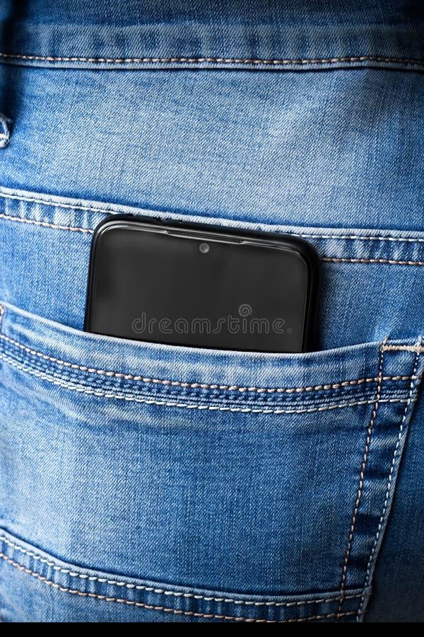 Teléfono en un bolsillo de jeans foto de archivo
