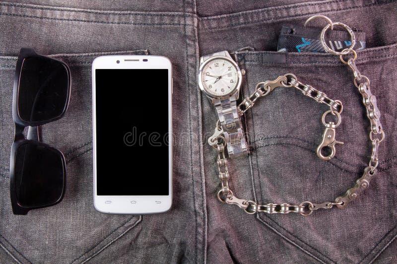 Teléfono, gafas de sol, reloj y cartera elegantes en fondo de los vaqueros foto de archivo