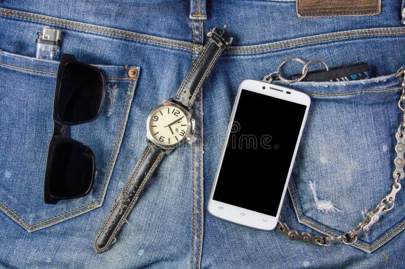 Teléfono, gafas de sol, reloj y cartera elegantes en fondo de los vaqueros fotos de archivo libres de regalías