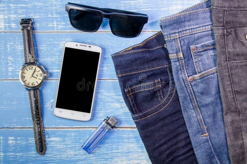 Teléfono, gafas de sol, vaqueros y reloj elegantes en backgr de madera azul foto de archivo libre de regalías