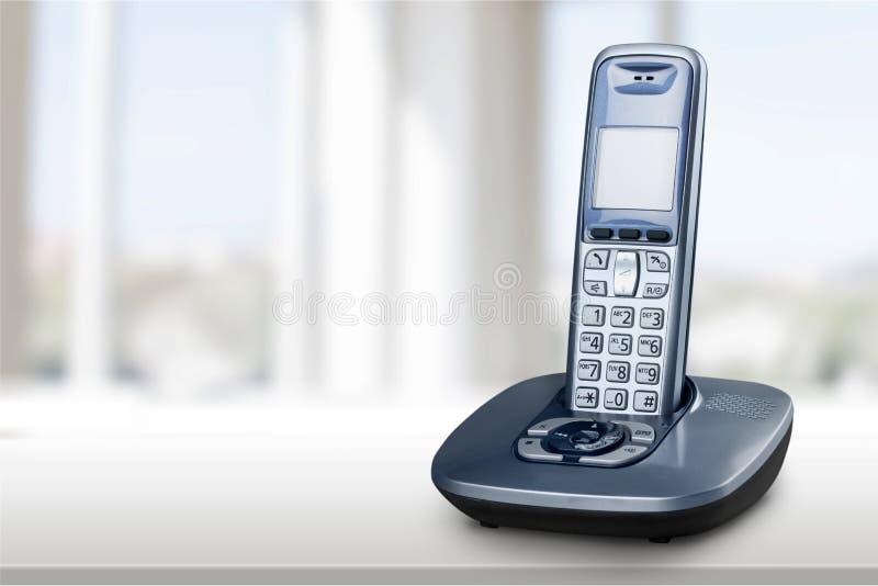 Teléfono inalámbrico con la cuna en el fondo blanco fotos de archivo