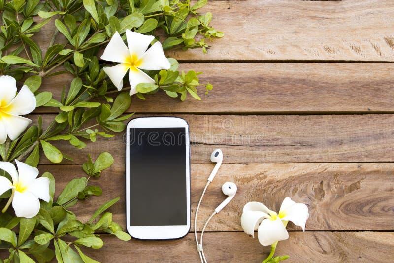 Teléfono móvil, auricular con las flores frangipani, hoja foto de archivo