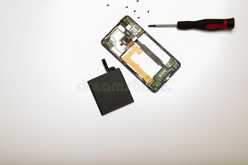 Teléfono móvil, batería, destornillador y tornillos desmontados imagen de archivo libre de regalías