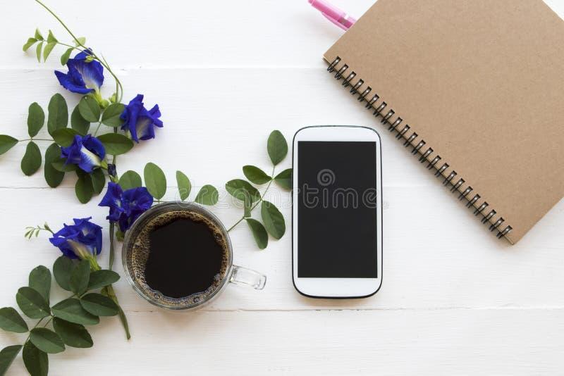 Teléfono móvil, café sólo con la flora local del guisante de mariposa de la flor de Asia imágenes de archivo libres de regalías