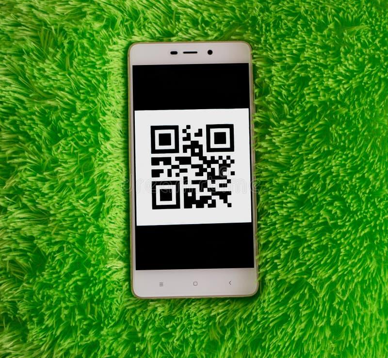Teléfono móvil con código de QR en la pantalla Hierba verde artificial imágenes de archivo libres de regalías