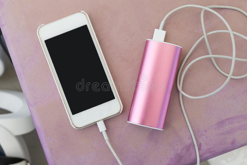 Teléfono móvil con el cargador del poder fotografía de archivo