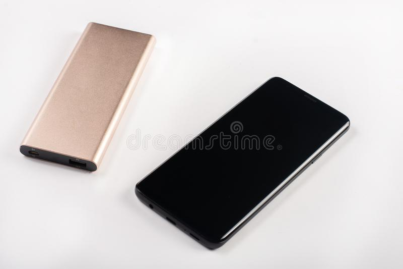 Teléfono móvil con el cargador externo del paquete de alimentación por USB fotos de archivo