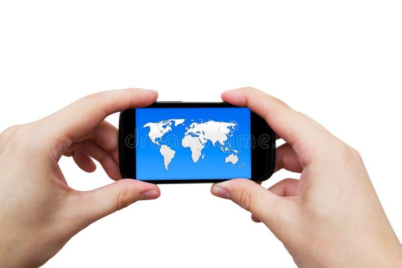 Teléfono móvil con el mapa del mundo en la exhibición fotografía de archivo libre de regalías