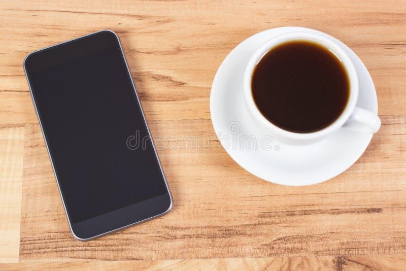 Teléfono móvil con la pantalla en blanco y la taza de café foto de archivo