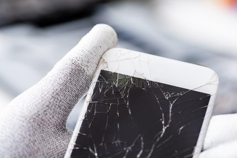 Teléfono móvil con la pantalla quebrada imagenes de archivo