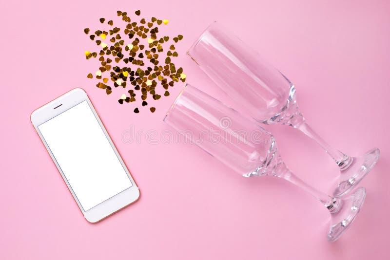 Teléfono móvil con los vidrios vacíos blancos de la pantalla y del champán con confeti de oro en estilo mínimo del papel rosado d fotos de archivo