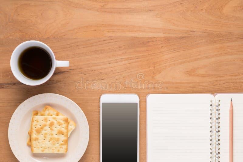 Teléfono móvil, cuaderno, lápiz, café, té, galleta de la comida imagen de archivo
