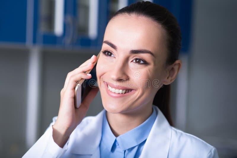 Teléfono móvil de custodia experto agradable lindo cerca de su cabeza y sonrisa imágenes de archivo libres de regalías