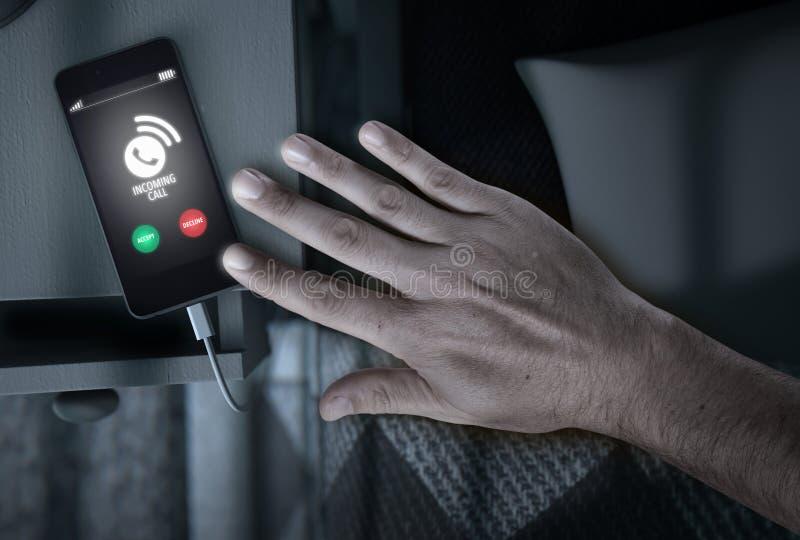 Teléfono móvil de la llamada entrante al lado de la cama fotos de archivo