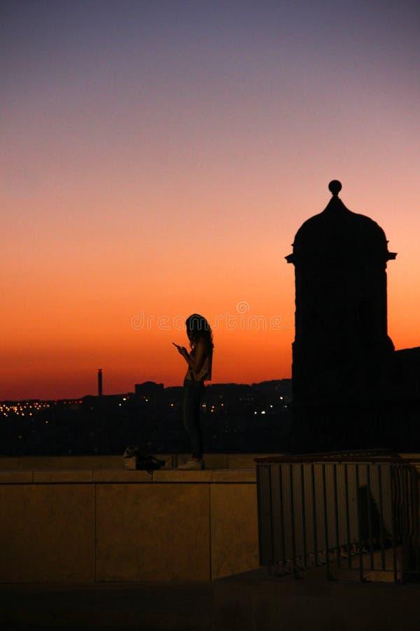 Teléfono móvil de la resaca de la mujer joven en fondo de la puesta del sol que brilla intensamente imágenes de archivo libres de regalías