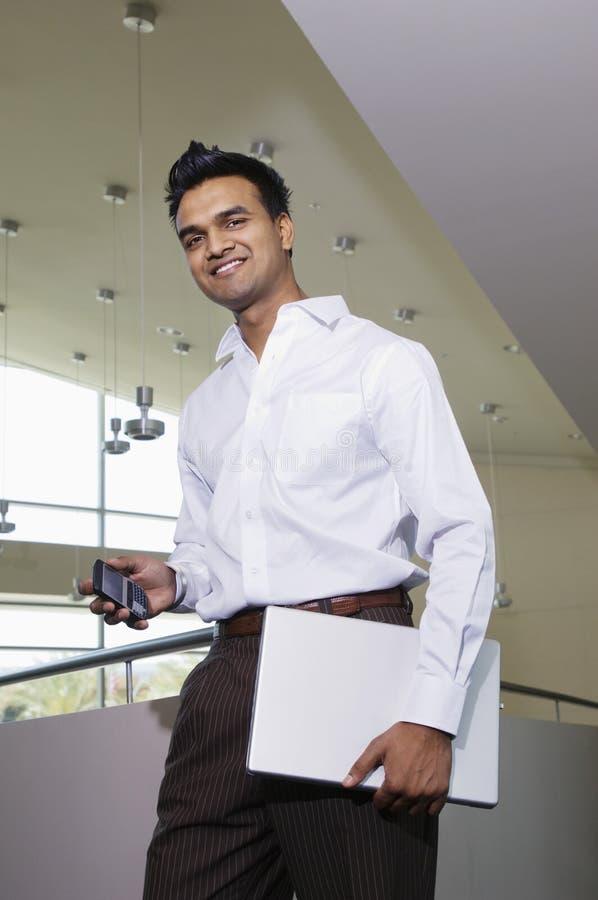Teléfono móvil de With Laptop And del hombre de negocios fotos de archivo libres de regalías