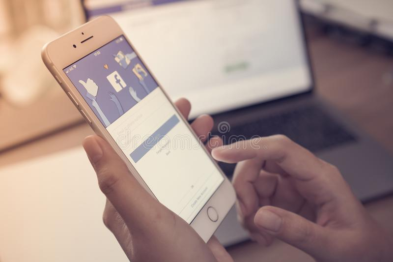 Teléfono móvil del iPhone intermedio social del app con el backgroun de la pantalla azul imágenes de archivo libres de regalías