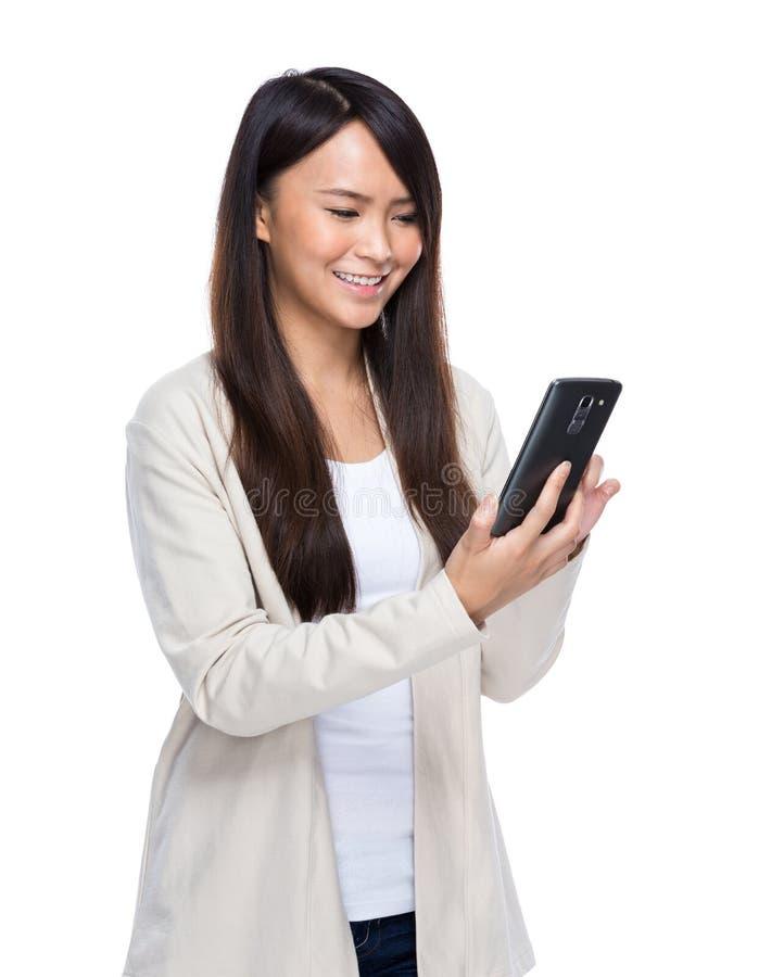 Teléfono móvil del uso asiático de la mujer joven fotografía de archivo libre de regalías