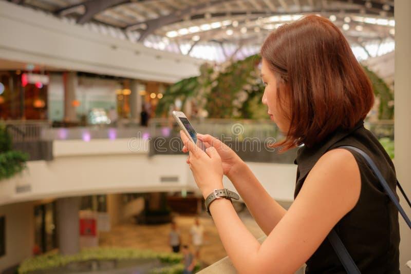 Teléfono móvil del uso de las mujeres jovenes en alameda de compras fotografía de archivo