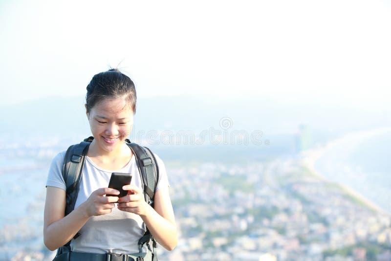 Teléfono móvil del uso del caminante de la mujer foto de archivo