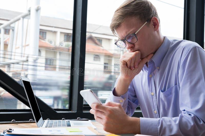 Teléfono móvil del uso pensativo del hombre de negocios en el lugar de trabajo textin del hombre fotos de archivo