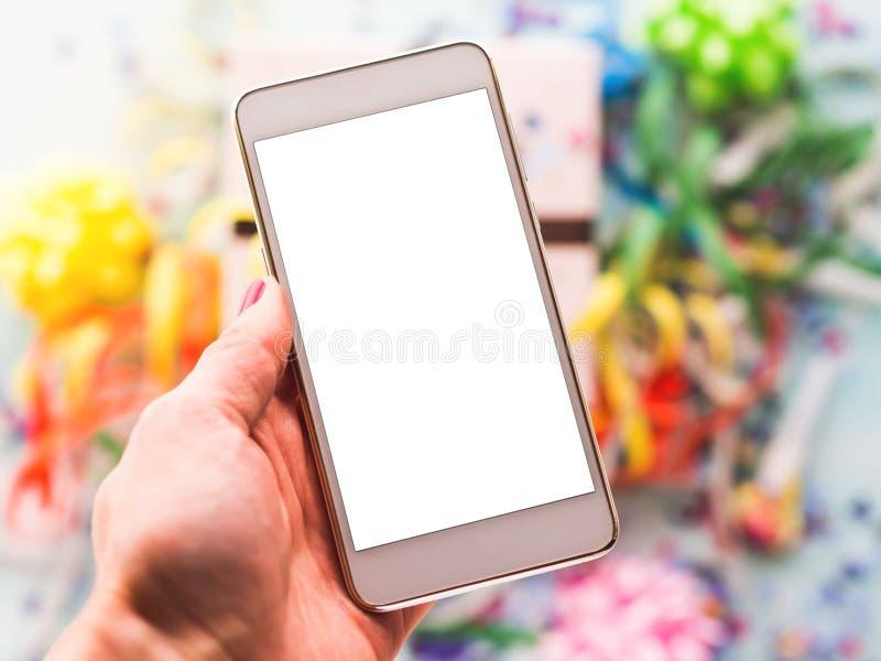 Teléfono móvil a disposición sobre la decoración del partido fotos de archivo libres de regalías