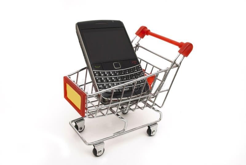 Teléfono móvil en carro de compras imagen de archivo