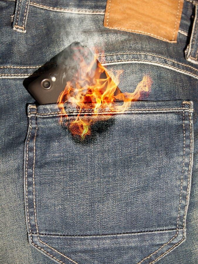 Teléfono móvil en el fuego imagen de archivo