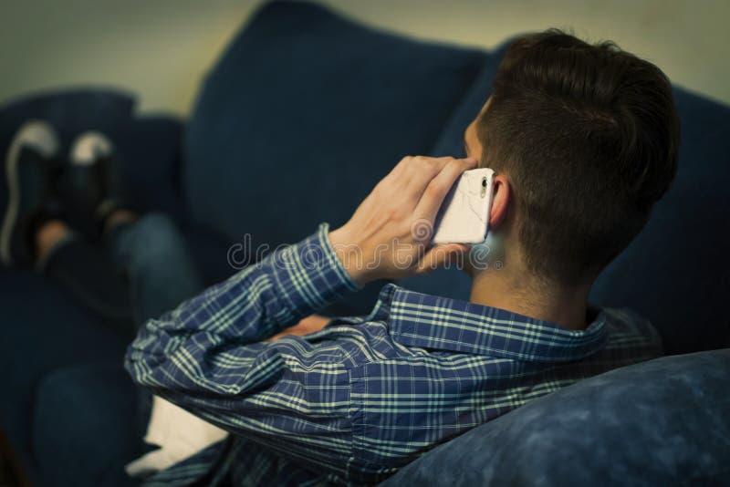 Teléfono móvil en el oído que escucha y que habla imagenes de archivo