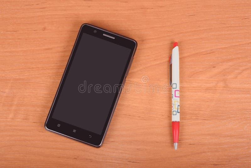 Teléfono móvil en fondo de madera fotografía de archivo